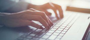 Image of woman writing a blog using a keyboard