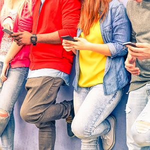 Image of group of young people checking cell phones.